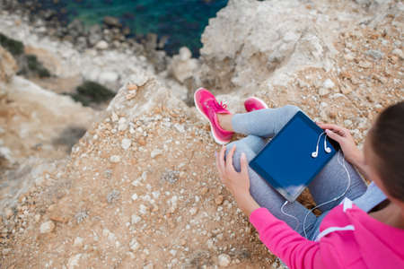 Woman in pink sneakers, a sports jacket pink, gray sweat pants and gray t-shirt, sitting in the open air, on the high rocky shore, against the blue of the ocean, ready to listen to music Stock Photo