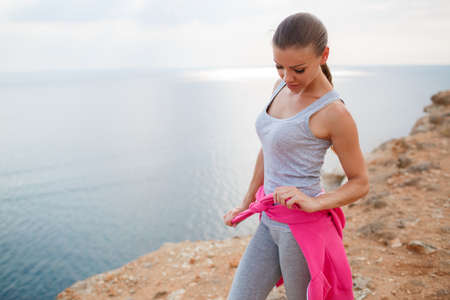 Athletic woman with a sweet smile, brunette, hair in a braid, full lips, wearing a gray t-shirt and gray sweat pants, pink sneakers and a pink sports jacket, wearing dark sunglasses, performing warm-up exercises on the rocky shore The blue ocean