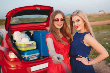 Young, slim, beautiful women, a blonde in a blue dress and a red-haired girl in a red dress, gray eyes, lovely smiles, long black eyelashes, red lipstick and makeup, two best friends are preparing to travel on a red car With suitcases and things