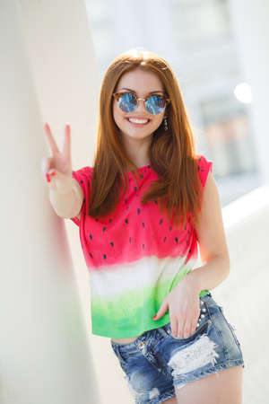 Young beautiful woman with long, red, straight hair, blue mirrored sunglasses, pretty makeup, pink plump lips, cute smile, spends time alone outdoors in the summer in the city, dressed in a red blouse and blue denim shorts, posing in the afternoon Sunligh Stock Photo