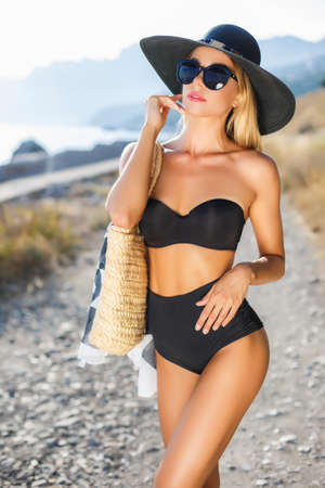 Young beautiful woman with a slender figure, blonde in dark sunglasses and a big black hat from the sun, black bikini, beach bag beige, posing alone outdoors in the summer against the backdrop of mountains, rocky beach and ocean