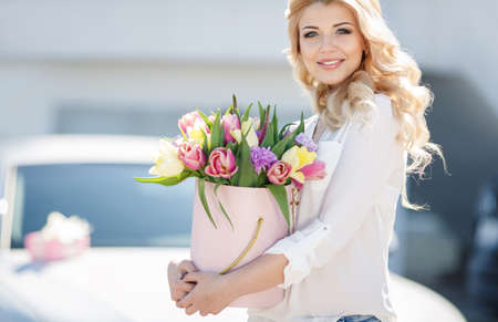 Beautiful young woman with blue eyes, blonde with long curly hair, stylish make-up dressed in blue jeans and a white shirt, spends time outdoors in the summer, one walks through a beautiful bouquet of tulips in your day