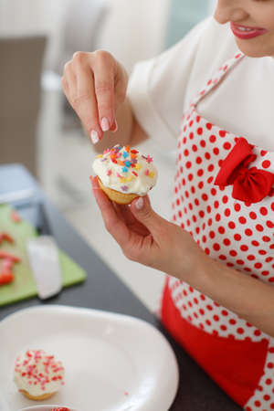 A caring housewife, a beautiful woman with long blonde curly hair, long black eyelashes and a nice smile, dressed in a white t-shirt with short sleeves and white apron for the kitchen with red polka dots, cooks in the kitchen cupcakes with strawberries