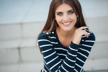 Young beautiful woman brunette with long straight hair and gray-green eyes, a nice smile and white straight teeth, light makeup, dressed in a striped t-shirt and blue jeans, spends time in the city in the spring, sitting on the steps, one in the fresh air