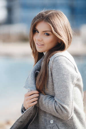Portrait of a beautiful young woman on an autumn deserted beach, light straight long hair, blue eyes, light make-up, sweet smile, pink lipstick, spends her time alone in the fresh air, walking near the sea, wearing a gray autumn coat