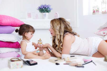 Een jonge mooie moeder, een blondine met lang krullend haar, gekleed in een witte trui en wit slipje, speelt op een wit bed in de slaapkamer met haar dochtertje, een brunette meisje met een mooi kapsel, gekleed in een tanktop en wit slipje , een familie