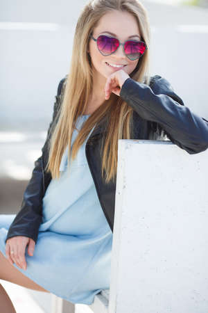 Happy young pregnant woman with long blond hair, beautiful smile and white equal teeth, wearing a mirror sunglasses of pink color in the form of hearts, dressed in a black leather jacket and blue dress, spends time alone in the open spring
