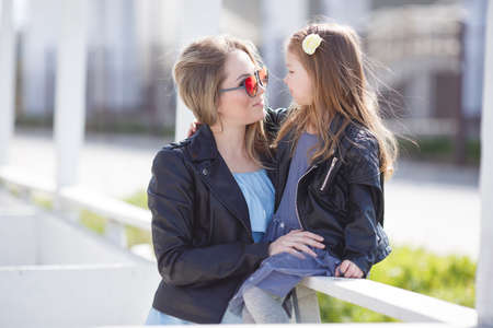 Happy family, mother, young pregnant woman with blond hair in sunglasses in the form of hearts and her little daughter, a girl of 5 years old with blond hair and gray-green eyes, both dressed in leather jackets black, to spend time outdoors in the summer