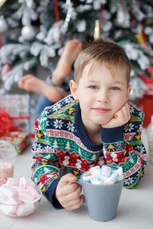Vijf jaar oude jongen met kort haar, gekleed in een lichte trui met kerstpatronen, op blote voeten liggend op de vloer onder een mooie, elegante kerstboom