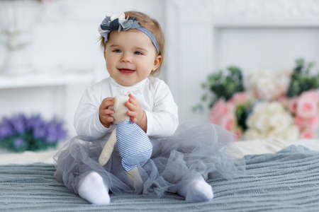 Little girl with brown eyes and red hair, but the head is wearing a gray-blue wreath with white and gray flowers, dressed in a white t-shirt and transparent gray-blue skirt, spends time alone, playing on a large bed in the bedroom Фото со стока