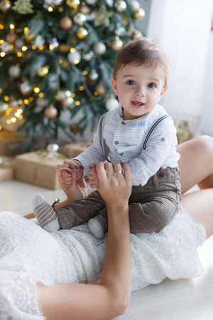 Happy family mother and little son near christmas tree on Christmas Eve at home. A woman and a little boy are resting in the white room near the Christmas tree. Family at home. A young mother playing with her son waiting for the New Year Stock Photo
