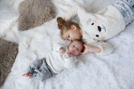 Little girl embracing a newborn baby brother. Little girl and baby boy, brother and sister playing in parents bed .Cute girl and a newborn boy resting together in a white bedroom. Family with children at home. Love, trust and tenderness
