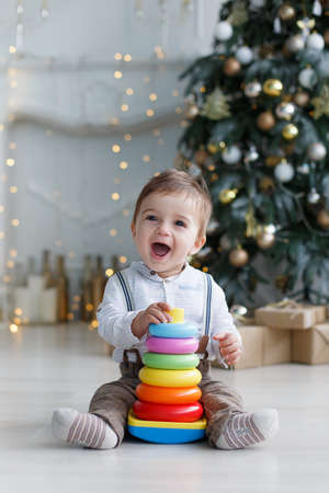 A little boy sits on a white glossy floor near a smart, green, Christmas tree with gift boxes under it, against the background of festive decorations and lights, one collects a multi-colored plastic pyramid