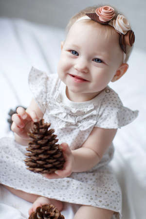 Close-up of a eight, nine months old baby girl with blue eyes. Newborn child, little adorable smiling and attentive girl looking surprised at the camera. Family, new life, childhood concept.Christmas Eve Stock Photo