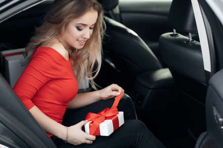 Young, beautiful, smiling woman in the back seat of the car opens the gift.A young, pretty woman, a blonde with long hair and a beautiful smile, dressed in a red dress, sitting in the back seat of a black car examines white gift boxes tied with red ribbons Stock Photo