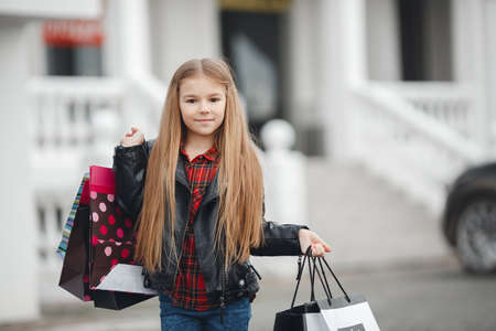 Stylish little girl with shopping bags with gifts. Happy child holds a lot of shopping bags with gifts. Black Friday sale holidays concept. Kids shopping Stock Photo