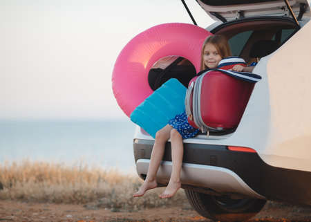 A cute little girl with light, long, straight hair, dressed in a blue dress in a white flower, bare feet, sits in the trunk of a white car, loaded with suitcases and things, the car stands on the beach in the open summer air