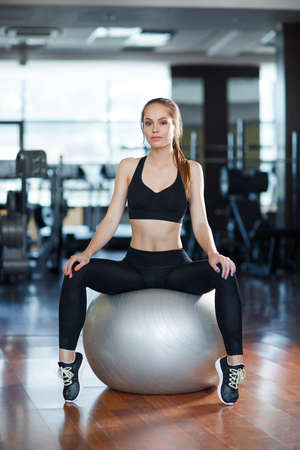 Young beautiful woman, model, brunette, hair group at a ponytail, dressed in a black open-type sports suit, slender figure, sweet smile, spends time in the fitness center, doing gym, holds a photo session , a healthy lifestyle