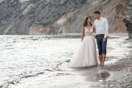 A beautiful bride and groom on their wedding day walk along a rocky shore near the sea.Young Couple On The Beach, Honeymoon, Happy Smiling Man And Woman Walking Seaside Sea Ocean Holiday Travel.Happy Wedding Day.