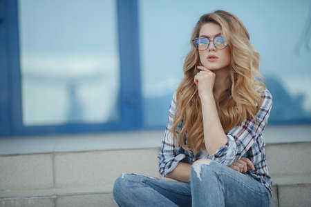 Beautiful woman with long, wavy hair and green eyes, beautiful makeup, pink plump lips, sweet smile, blonde, spending time outdoors in the summer in the city, dressed in a white jersey and checkered shirt, posing sitting on the steps, wearing glasses