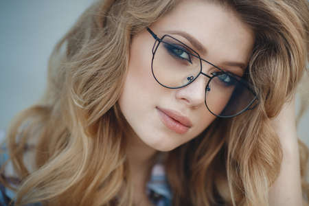 Beautiful young woman with long, thick, wavy hair, multi-colored make-up, long black eyelashes, plump pink lips, posing in studio on a blue background, portrait of a cute woman with an elegant hairstyle and perfect make-up, wear glasses Stock Photo