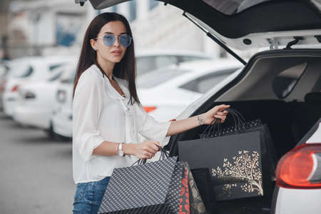 Beautiful brunette young woman with shopping bag near the white super car, outdoors. Woman standing near the white car happy driver.Young woman in blue glasses next to the car.Happy woman putting colorful bags after shopping into car.Shopping by car Banco de Imagens