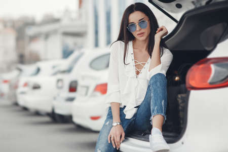 Beautiful brunette young woman with shopping bag near the white super car, outdoors. Woman standing near the white car happy driver.Young woman in blue glasses next to the car.Happy woman putting colorful bags after shopping into car.Shopping by car Stockfoto