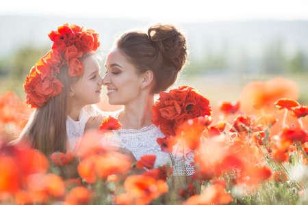 Mother and daughter in a field of poppies. Beautiful mother and her daughter playing in spring flower field. A little girl in a red wreath of fresh flowers walking on the poppy field with her mother on a Sunny summer day