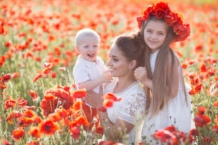 Mother, son and daughter in a field of red poppies. Happy mother with little son and daughter in spring flower field. A little girl in a red wreath of fresh flowers walking on the poppy field with mom and brother on a Sunny summer day