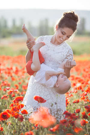 A beautiful young mother in a white dress with a young son in her arms enjoying the beauty of the blooming red flowers, walking through a huge meadow on a sunny summer day.Summer scene of a happy mother and son in the field of red poppies