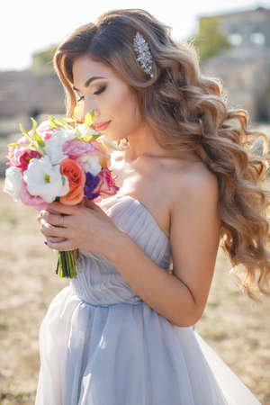 Young beautiful woman, bride in a light blue long wedding dress, blonde with long, thick, curly hair, bare shoulders, in her right hand holding a beautiful bouquet of flowers, posing alone, standing outdoors on a sunny day