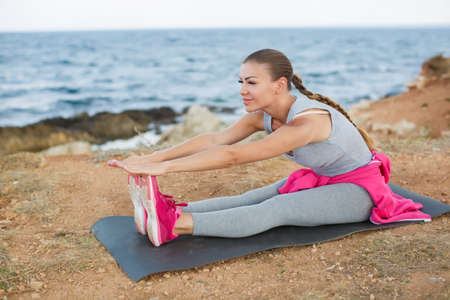 A sporty woman doing warm-up exercises on a rocky blue ocean shore, sitting on an athletic rug Stock Photo