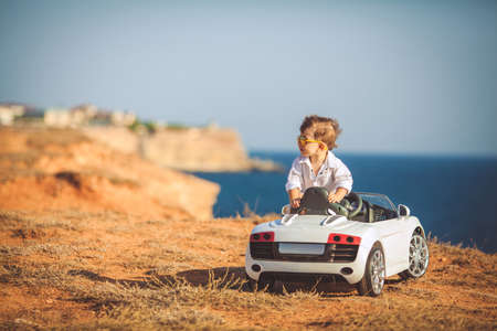 The little boy, the driver with a fashionable hairstyle, brown hair, wears mirrored, sun glasses, gold, wearing a white fashionable shirt, running a child's electric car, a white convertible, posing outdoors in the summer on the rocky coast of the ocean