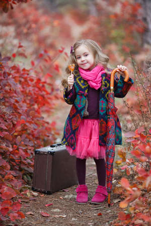 Cute little girl playing with fallen golden leaves. Happy child walking in autumn park. Beautiful golden autumn time. Autumn kids fashion. Raincoat during the rain. Standard-Bild