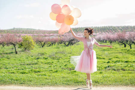 Fashion Art Mystic Spring Model Girl Portrait Spring Sunny Day. Beautiful woman with a sweet smile, curly brown hair fairy with pink balloons Stock Photo - 114592583