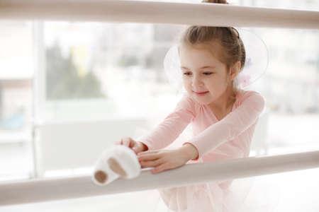 Little ballet girl in ballet studio. Little ballerina girl in a pink tutu. Adorable child dancing classical ballet in a white studio. Children dance.Young gifted dancer in a class. Preschool kid taking art lessons. Little Ballet Star