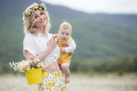 A newborn son is standing outdoors in the highlands among a blooming chamomile field. Blue sky and white meadows of blooming daisies Imagens
