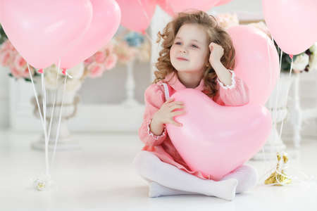 Fashion little girl model fece close up. Face female kid wiht happy emotion. Little girl hold heart, fathers, mothers day. Valentines day, love, birthday. Childhood, happiness, copy space Small girl child with a pink heart-shaped balloon