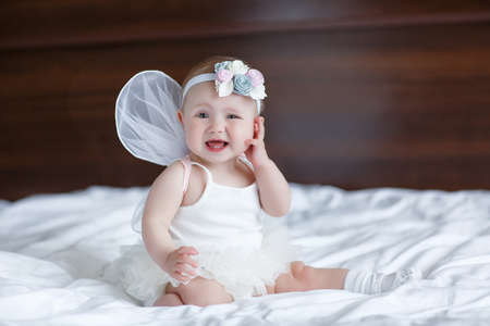 Happy little baby with angel wings. Blue-eyed baby with angel wings behind him. Newborn with Angel Wings. Child Sitting at Blue Sky Cloud. Girl 5-7 months sitting on white bed in the bedroom. Newborn angel Stock fotó