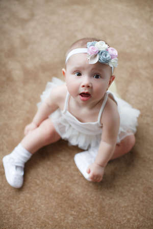 Crawling on the bed. Girl crawling on bed and laughing. Happy healthy little child at home. Infant kid in sunny nursery.A child of 5 months is having fun, sitting on a snow-white bed.