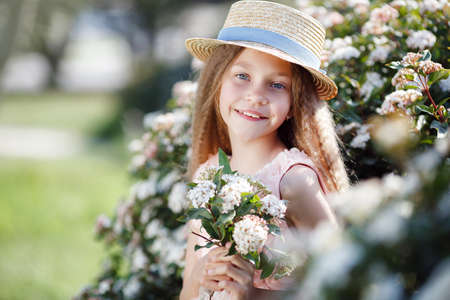 Portrait of a beautiful happy girl enjoying smell in a flowering spring blooming garden. Bright and fashionable smiling girl near blossom. Landscape. Spring portrait of a smiling girl in a hat Stock Photo