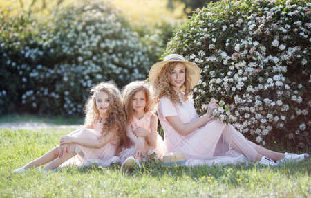The older sister and her two younger sisters spend time outdoors in a beautiful park with a flowering shrubs on a sunny spring day. Three sisters in pale pink dresses with straw hats in their hands on a background of flowers