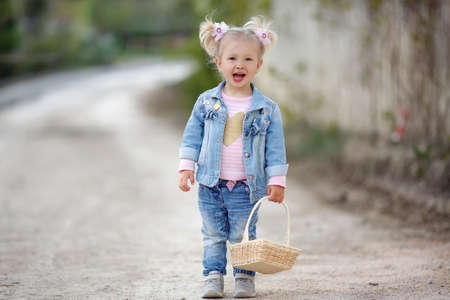 Little girl in the countryside on the country road in the countryside with a basket. Banco de Imagens