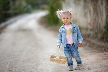 Little girl in the countryside on the country road in the countryside with a basket. 스톡 콘텐츠