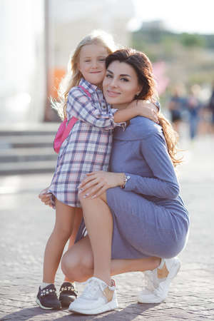 Mother and daughter outdoors in city. playing and having fun. Happy little girl and baby daughter in bright sunlight. Beautiful portrait. Real emotions.