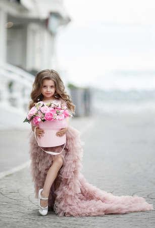 Lovely little girl holding a bucket of roses