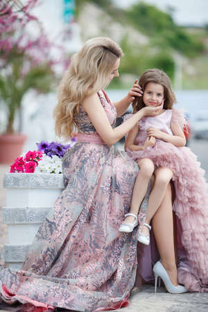 Happy young woman in evening dress with her daughter. Pink ball gowns in summer near the palace.