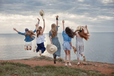Five girls having fun on the beach. The lighthouse and the coastline.
