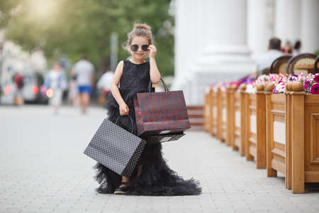 Cute little caucasian girl child having shopping fun. Fashion trend. Fashion shop. Little girl with bunch packages. Seasonal sale. Fashion girl customer. Happy child in shop with bags. Shopping day happiness. Birthday girl shopping. Fashion boutique