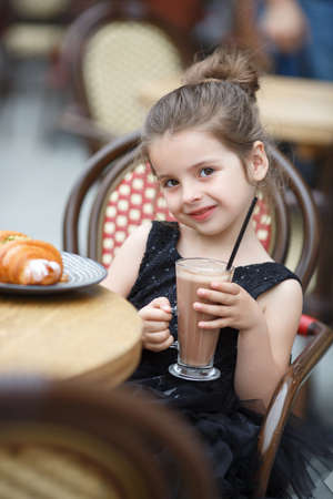 It is a cute little girl. Adorable little girl having lunch at an outdoor cafe. Girl alone in an outdoor cafe Imagens